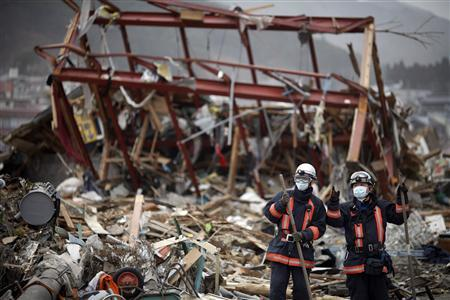 Japanese rescue workers pause from their operation in the destroyed residential part of Ofunato more than a week after the area was devastated by an earthquake and tsunami March 20, 2011. REUTERS/Damir Sagolj