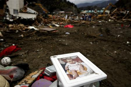 A photo of a baby is saved from the ruins of a collapsed house as rescue workers search for victims in tsunami-devastated Rikuzentakata March 21, 2011. REUTERS/Damir Sagolj