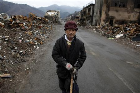 Resident Kaga Toraki, 73, stands on a road between debris in Otsuchi, Iwate March 21, 2011. REUTERS/Aly Song