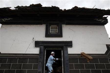 A rescue worker clears debris from a house as he searches for victims of a tsunami in devastated Rikuzentakat March 21, 2011. REUTERS/Damir Sagolj