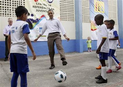 President Obama kicks a soccer ball with children during his visit to the Ciudad de Deus Favela neighbourhood in Rio de Janeiro, March 20, 2011. REUTERS/Jason Reed