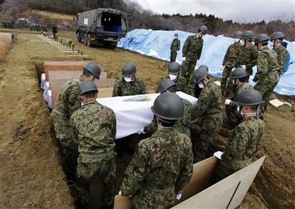 Members of the Japan Ground Self Defense Force carry the coffin of a victim of the tsunami at a temporary mass grave site in Higashi Matsushima, northern Japan March 23, 2011. REUTERS/Yuriko Nakao