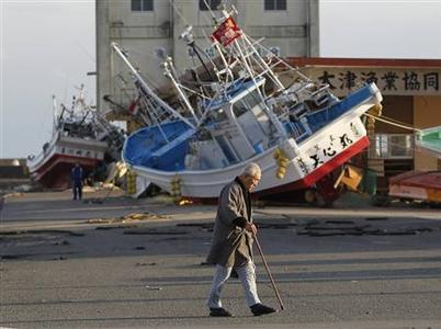 Hiroshi Murayama, 82, walks past ships that were washed to shore, at Otsu port in Kitaibaraki, Ibaraki prefecture, March 23, 2011. REUTERS/Toru Hanai