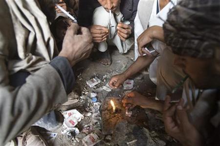 Afghans smoke heroin at a cave in southern Herat November 2, 2009. REUTERS/Morteza Nikoubazl