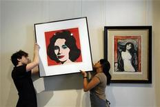 "<p>Workers adjust Andy Warhol's ""Elizabeth Taylor"" hanging beside Edvard Munch's ""Madonna"" at Bonhams auction house in London July 9, 2010. REUTERS/Stefan Wermuth</p>"