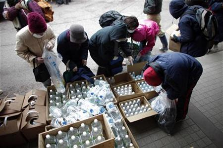 People collect bottles of mineral water at a food distribution in Yamada, Iwate Prefecture in northern Japan, March 24, 2011. REUTERS/Carlos Barria