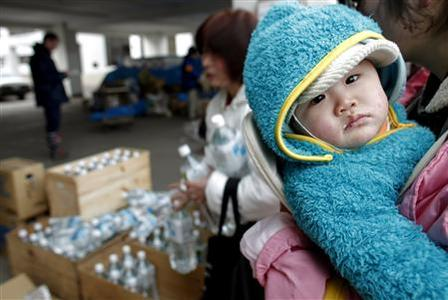 A woman holds a baby as a family member collects bottles of mineral water at a food distribution in Yamada, Iwate Prefecture in northern Japan, March 24, 2011. REUTERS/Carlos Barria
