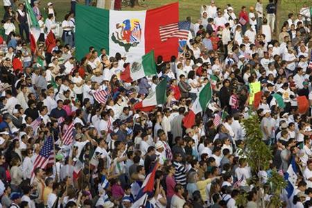 Demonstrators wave Mexican and the United States flags and cheer at a planned protest near downtown San Diego, California May 1, 2006. REUTERS/Fred Greaves