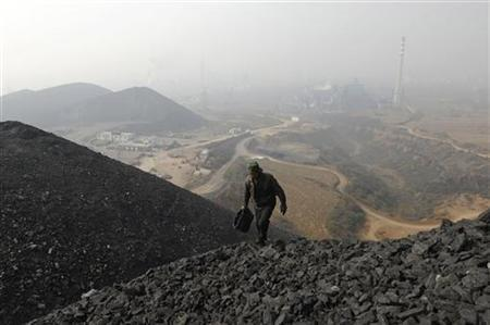 A labourer searches for usable coal at a cinder dump site on the outskirts of Changzhi, Shanxi province October 27, 2009. REUTERS/Stringer