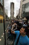 <p>Alex Lee, touriste canadien et premier dans la file d'attente devant l'Apple Store du quartier des affaires de Sydney, converse avec des amis britanniques grâce à son premier iPad 2, acheté il y a deux semaines aux Etats-Unis. La nouvelle version de la tablette numérique d'Apple est lancée vendredi dans 25 pays. /Photo prise le 25 mars 2011/REUTERS/Tim Wimborne</p>