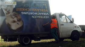 <p>Рабочие демонтируют билборд с изображением члена партии ХДС Штефана Маппуса в пригороде Штутгарта, 28 марта 2011 года. Партия консерваторов, возглавляемая канцлером Ангелой Меркель, в воскресенье проиграла на выборах на юго-западе Германии. REUTERS/Michael Dalder</p>