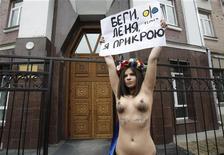 <p>Активистка украинской женской организации Femen держит плакат в защиту экс- президента страны Леонида Кучмы, 28 марта 2011 года. Известные эпатажным поведением активистки украинской женской организации Femen в понедельник утром разделись по пояс под стенами генпрокуратуры в знак солидарности с экс- президентом Леонидом Кучмой, отрицающим обвинения убийству к оппозиционного журналиста. REUTERS/Gleb Garanich</p>