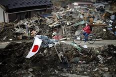 """<p>Женщина проезжает мимо лежащего на земле флага Японии, 29 марта 2011 года. Плутоний был обнаружен во вторник в почве на территории японской атомной станции """"Фукусима-1"""", вышедшей из строя после сильнейшего землетрясения. REUTERS/Carlos Barria</p>"""
