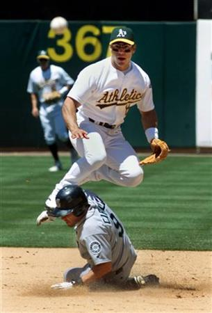 Seattle Mariner baserunner Jeff Cirillo (9) is out at second as Oakland A's second baseman Randy Velarde goes high in the air in the fifth inning of a game in Oakland, California, on June 6, 2002. Velarde testified on Wednesday that he used drugs he believed were human growth hormone obtained from home run king Barry Bonds' personal trainer. REUTERS/Lou Dematteis