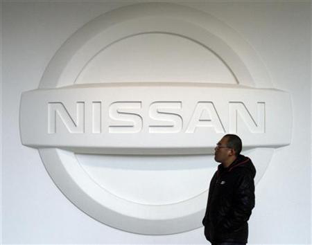 A man walks past a logo of Nissan Motor Co at the company's global headquarters in Yokohama, south of Tokyo February 9, 2011. REUTERS/Toru Hanai