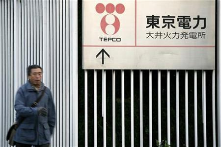 A man walks past a sign at the Oi thermal power station of Tokyo Electric Power Company, Inc. (TEPCO) in Tokyo in this January 26, 2009 file photo. REUTERS/Stringer/Files