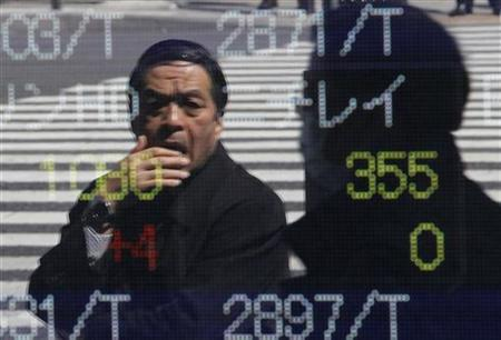 A man is reflected on a stock quotation board outside a brokerage in Tokyo March 28, 2011. REUTERS/Toru Hanai