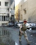 <p>A soldier walks past the site of a bomb attack in Baghdad March 29, 2011. REUTERS/Mohammed Ameen</p>