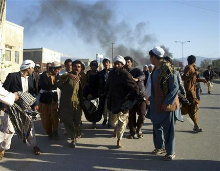 Afghans carry a man who was wounded following an attack on an United Nations compound, during a demonstration to condemn the burning of a copy of the Muslim holy book by a U.S. pastor, in Mazar-i- Sharif April 1, 2011. REUTERS/Stringer