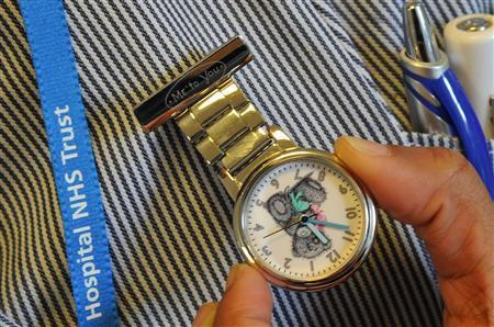 A nurse holds her watch in an outpatients ward at a hospital in west London April 4, 2011. REUTERS/Toby Melville