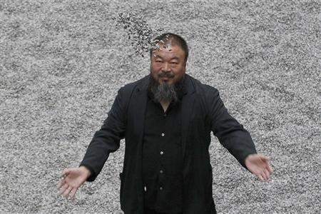 Chinese artist Ai Weiwei throws porcelain sunflower seeds into the air as he poses with his installation ''Sunflower Seeds'', in the Turbine Hall at the Tate Modern gallery, in London in this October 11, 2010 file photo. REUTERS/Stefan Wermuth/Files