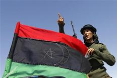 <p>A rebel fighter gestures beside a Kingdom of Libya flag on a pick-up truck at a staging area to the east of Brega April 4, 2011. REUTERS/Youssef Boudlal</p>