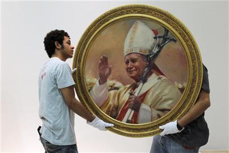 Workers hold a painting of the late pope John Paul II during the staging of the exhibition ''Karol Josef Wojtyla'' at the Villacero exhibition hall in Monterrey, April 22, 2010. REUTERS/Tomas Bravo