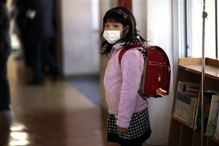 A girl waits outside her classroom on the first day of school at Shimizu elementary school in Fukushima, northern Japan April 6, 2011. REUTERS/Carlos Barria