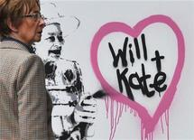 <p>A woman passes graffiti by British street artist Rich Simmons, depicting Queen Elizabeth, in London, April 1, 2011. REUTERS/Toby Melville</p>