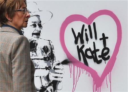 A woman passes graffiti by British street artist Rich Simmons, depicting Queen Elizabeth, in London, April 1, 2011. REUTERS/Toby Melville