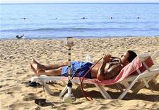 <p>A man sunbathes as he smokes a waterpipe at a public beach in Beirut, December 2,2010. REUTERS/Jamal Saidi</p>