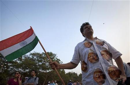 A demonstrator wearing portraits of social activist Anna Hazare on his shirt carries an Indian national flag during a protest rally against corruption in Mumbai April 8, 2011. REUTERS/Vivek Prakash