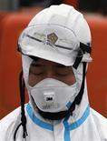 <p>Сотрудник полиции в защитном костюме стоит во время минуты молчания в память о погибших 11 марта, Минамисома (Япония), 11 апреля 2011 года. Японские власти могут расширить в некоторых местах зону отчуждения вокруг аварийной АЭС в Фукусиме, если за ее пределами будут обнаружены высокие уровни радиации. REUTERS/Kim Kyung-Hoon</p>