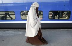 <p>Kenza Drider, a French Muslim of North African descent, wearing a niqab, walks on a platform as she arrives at the Gare de Lyon railway station in Paris April 11, 2011. REUTERS/Jean-Paul Pelissier</p>