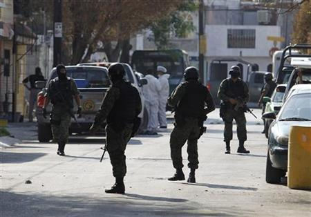 Soldiers patrol a crime scene in the municipality of Apodaca, neighbouring Monterrey March 23, 2011. Soldiers killed three hitmen during a gunfight after an anonymous call led federal forces to a safe house, according to local media. During the operation, the army freed one man kidnapped last week and seized ammunition, weapons and three vehicles. REUTERS/Tomas Bravo