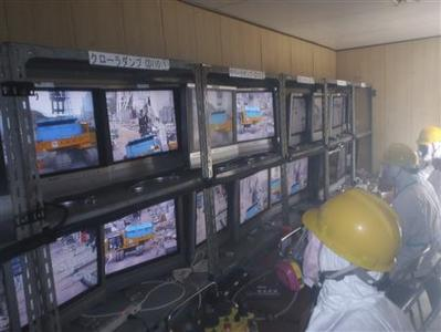 Workers in protective suits operate remote-controlled machinery to clear debris in the compound of Tokyo Electric Power (TEPCO) Co.'s crippled Fukushima Daiichi Nuclear Power Plant in Fukushima, northern Japan April 10, 2011, in this handout photo released by TEPCO April 11, 2011, one month after the 9.0 magnitude earthquake and a huge tsunami battered Japan's northeast coast. REUTERS/Tokyo Electric Power Co/Handout