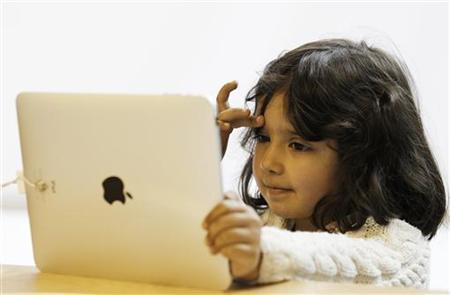 A girl views a new iPad tablet computer at an Apple store during its UK launch in central London, May 28, 2010. REUTERS/Luke MacGregor