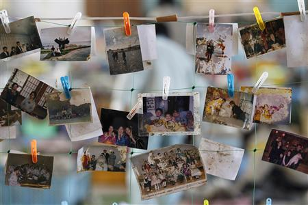 Photographs found in the rubble are hung at a collection center for those who are looking for their personal belongings in Natori, northern Japan, April 12, 2011. REUTERS/Kim Kyung-Hoon