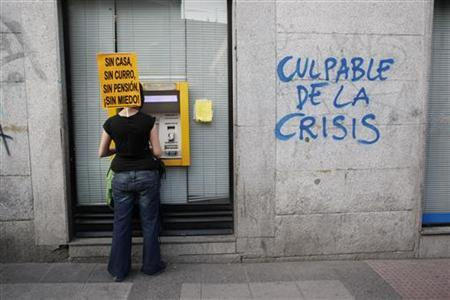 A protester carrying a banner that reads ''No home, no job, no pension, no fear'' withdraws money from an ATM machine next to graffiti sprayed by other protesters during a demonstration in Madrid, April 7, 2011. REUTERS/Susana Vera