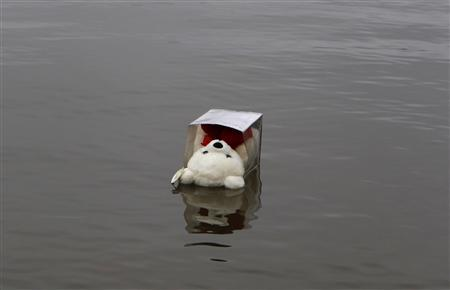 A child's teddy bear, left by a mourner, floats near a boat launch into the Hudson River, where a mother and several children were found dead in Newburgh, New York, April 13, 2011. REUTERS/Mike Segar