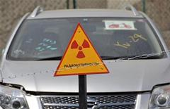 """<p>Автомобиль из Японии стоит за знаком """"Радиоактивность!"""" в порту Владивостока 14 апреля 2011 года. В порту Владивостока скопилось уже 49 автомашин, доставленных из Японии с радиоактивным загрязнением, сообщила портовая администрация, предупредив, что опасные грузы скоро будет негде складировать. REUTERS/Yuri Maltsev</p>"""
