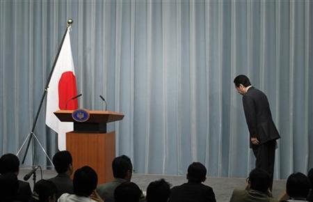 Japan's Prime Minister Naoto Kan bows to the national flag as he arrives at a news conference at his official residence in Tokyo, April 12, 2011. REUTERS/Yuriko Nakao