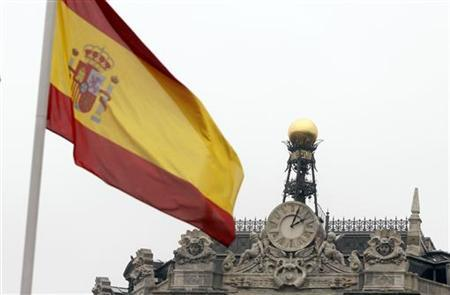 A Spanish flag flutters near the dome of the Bank of Spain in central Madrid February 15, 2010. REUTERS/Sergio Perez