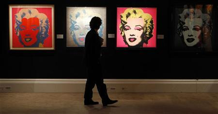 A Sotheby's employee poses in front of four screenprints all entitled ''Marilyn Monroe'' by Andy Warhol at Sotheby's in London September 13, 2010. REUTERS/Suzanne Plunkett