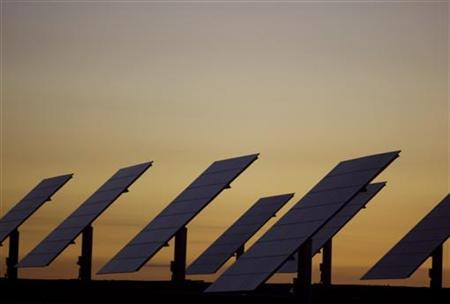 The sun sets beyond solar panels at a power plant in Amareleja, southern Portugal, April 23, 2008. REUTERS/Jose Manuel Ribeiro