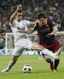 <p>Alvaro Arbeloa, do Real Madrid, disputa bola com Lionel Messi, do Barcelona, durante partida entre as duas equipes, válida pelo Campeonato Espanhol neste sábado, 16 de abril de 2011. O jogo acabou empatado em 1 x 1. REUTERS/Juan Medina</p>