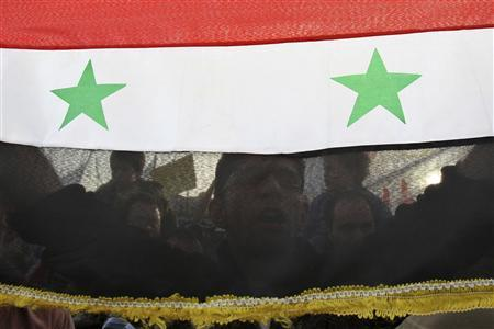 A Syrian protester holding his national flag shouts slogans calling for Syria's President Bashar al-Assad to step down during a protest in front of the Syrian embassy in Amman April 17, 2011. REUTERS/Muhammad Hamed