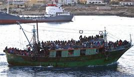 <p>Беженцы из Туниса подплывают к итальянскому острову Лампедуза, 8 апреля 2011 года. Франция в воскресенье временно закрыла свою границу для поездов, везущих из Италии африканских иммигрантов. Рим выразил официальный протест, обвинив Париж в нарушении принципов Евросоюза. REUTERS/Antonio Parrinello</p>