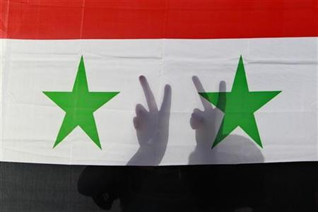 A Syrian protester gestures victory signs behind their national flag as they shout slogans calling for Syria's President Bashar al-Assad to step down during a protest in front of the Syrian embassy in Amman, Jordan, April 17, 2011. REUTERS/Muhammad Hamed