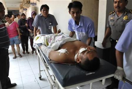 Medical workers carry a bomb victim at Pelabuhan hospital in Cirebon April 15, 2011. REUTERS/Shan Shan